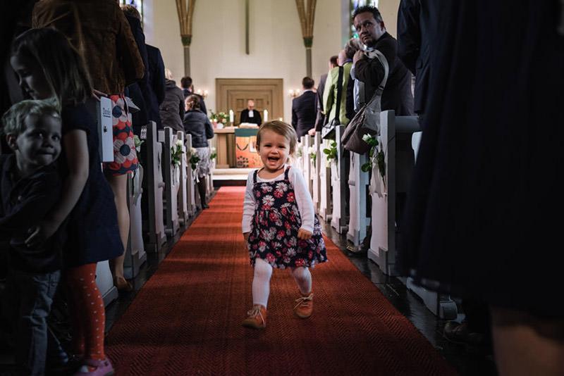 Kind rennt durch Kirchengang bei der kirchlichen Trauung