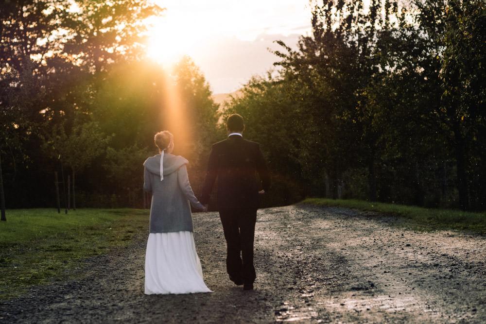 Hochzeitspaar geht Hand in Hand Richtung Sonnenuntergang am Gut Forkscheid