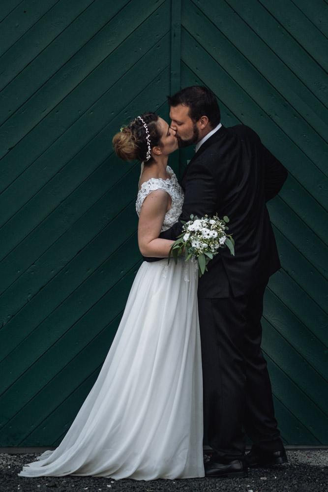 Hochzeitspaar küsst sich vor grünem Tor