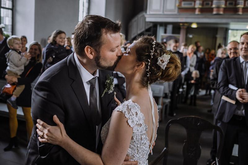 Brautpaar küsst sich bei Trauung in der Kirche Delling