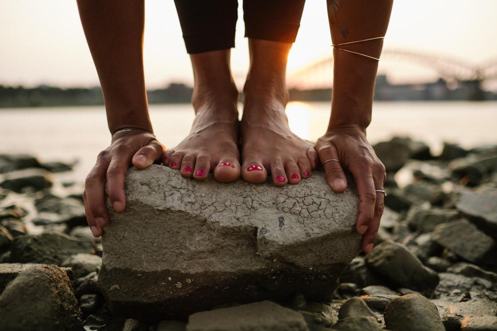 Yoga Stehende Vorbeuge Uttanasana vor Sonenuntergang am Rhein