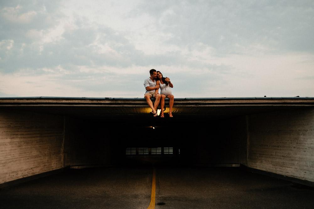 Schwangeres Paar sitzt auf Parkdeck
