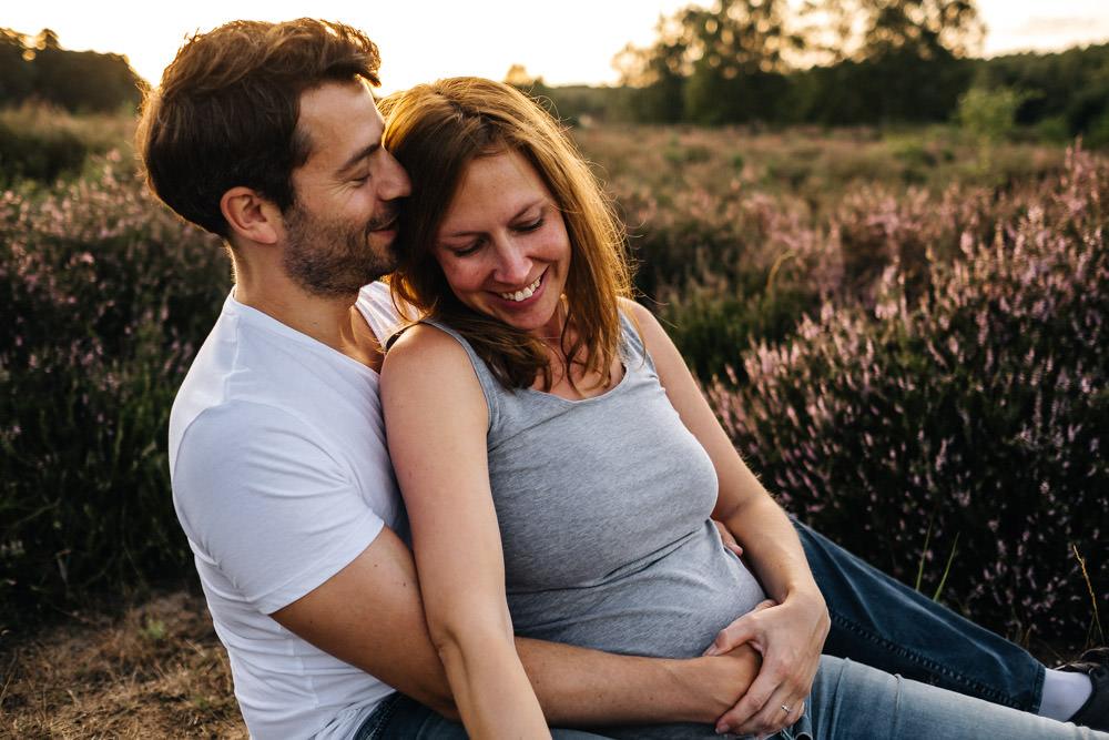 Schwangere Frau kuschelt sich an Mann Babybauchshooting