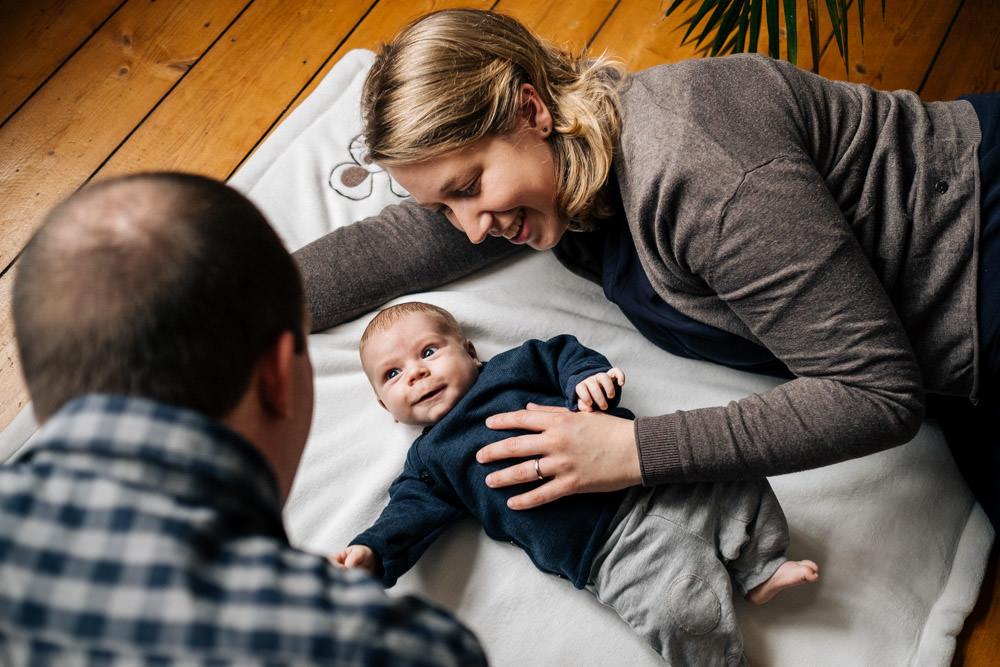Baby und Eltern auf einer Decke