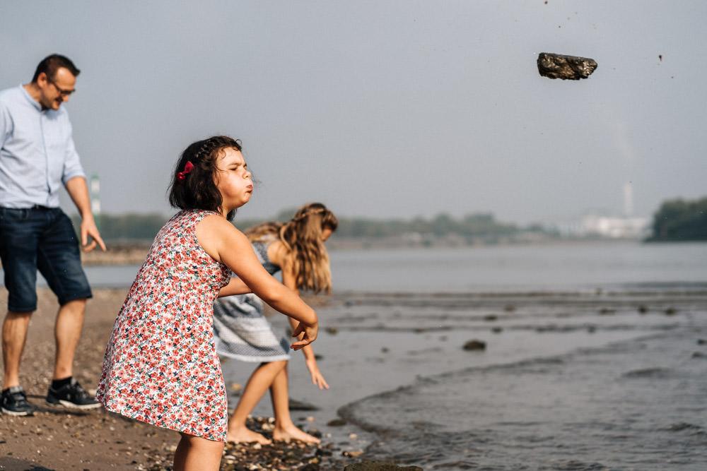Familienfotografie in der Natur Kind wirft Stein ins Wasser