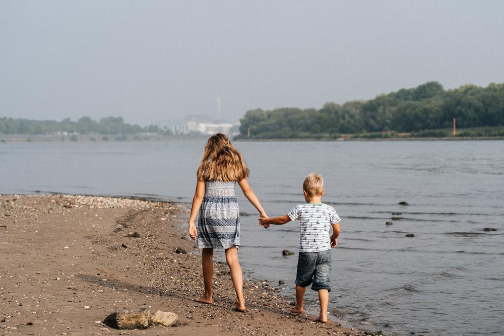 Schwester und Bruder spazieren am Strand