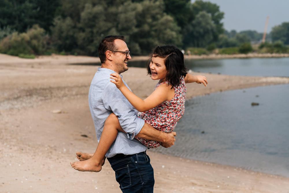 Tochter und Vater spielen am Strand