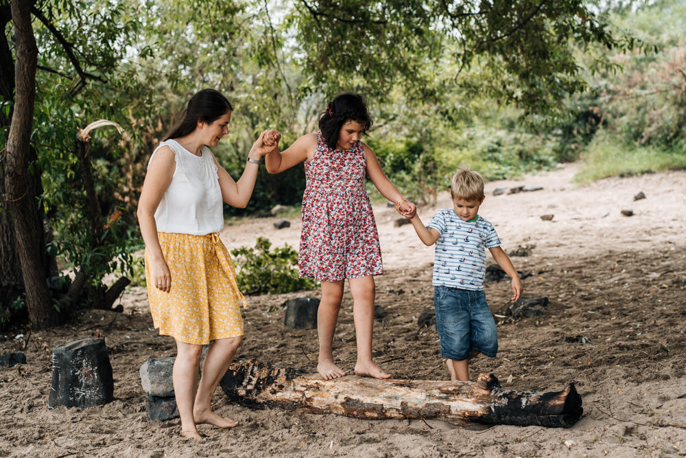 Tochter balanciert auf Baumstamm