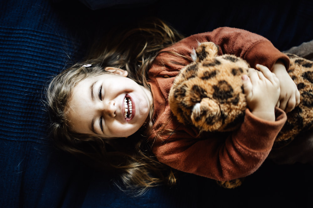 Kind lacht mit Kuscheltier