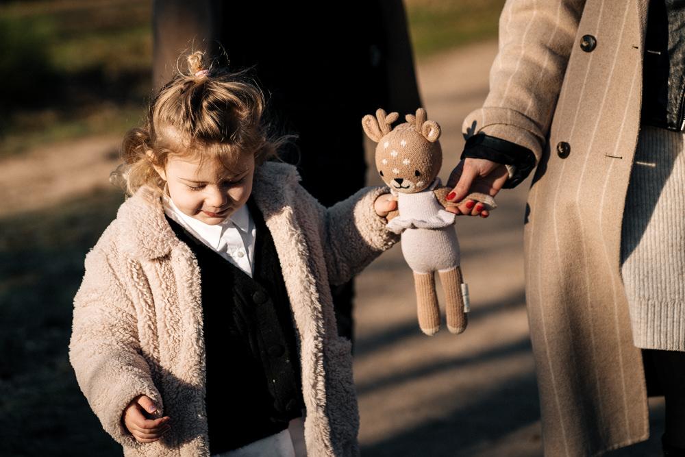 Tochter hält Händchen mit Kuscheltier und Mama Familienfotos