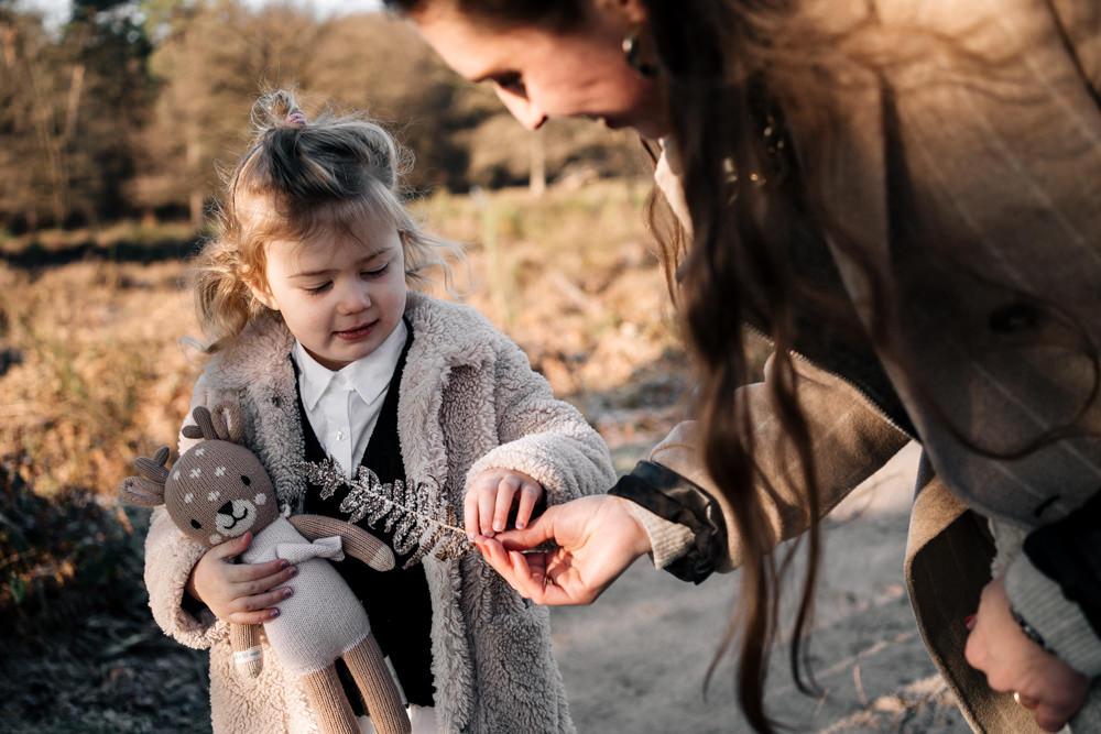 Mutter zeigt Tochter ein gefrorenes Blatt Familienreportage