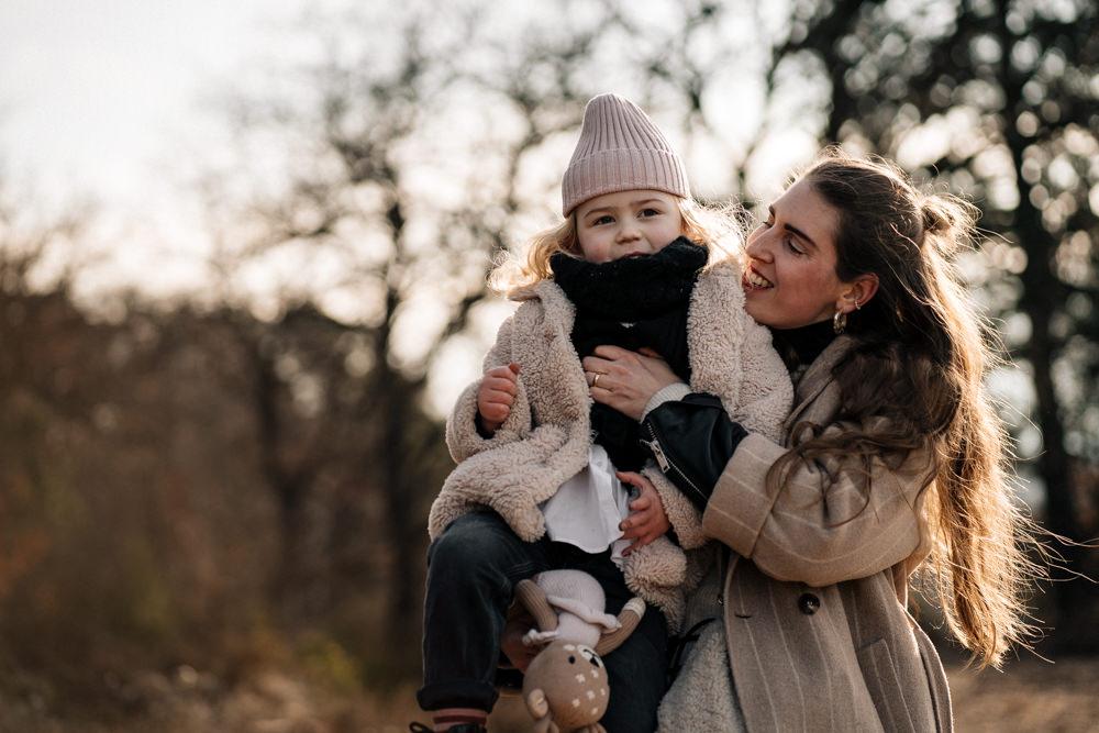 Mutter hält Tochter auf dem Arm Familienreportage