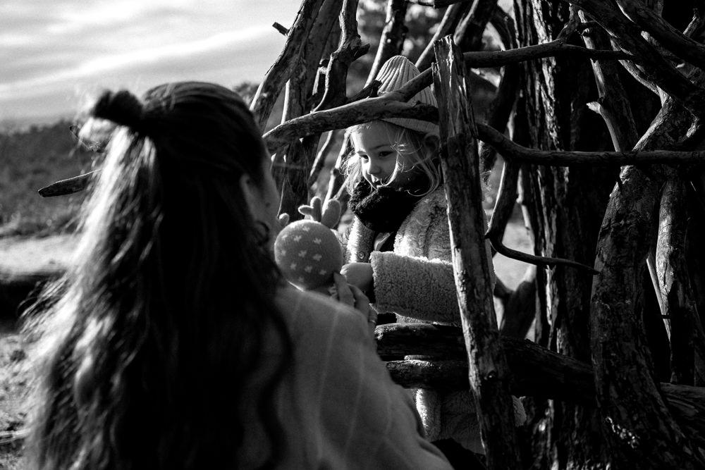 Mädchen schaut durch Holz Tipi zu ihrer Mama