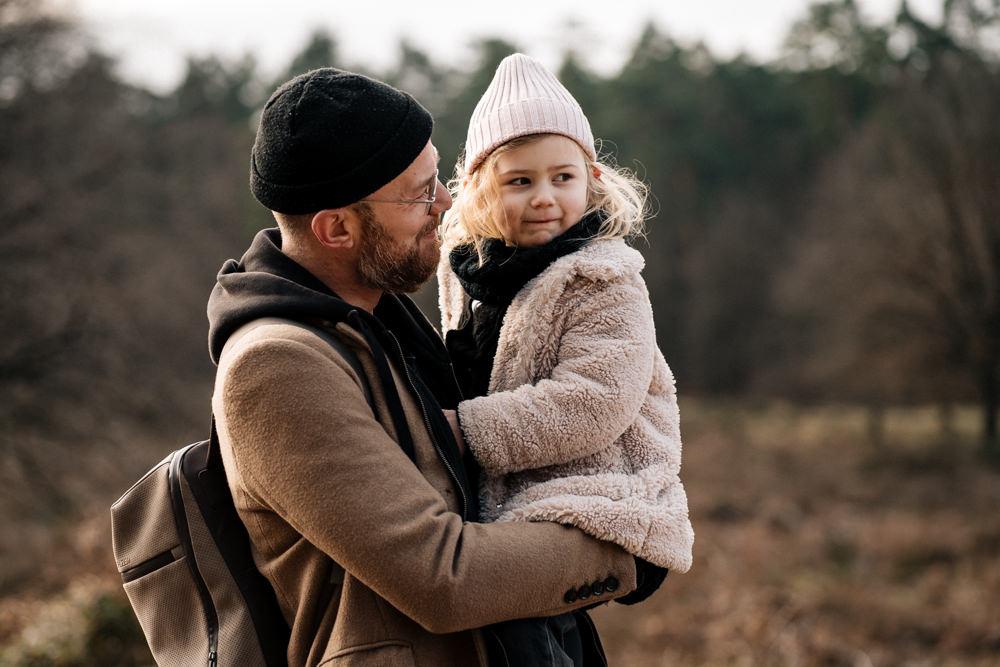 Blondes Mädchen bei Papa auf dem Arm familienreportage