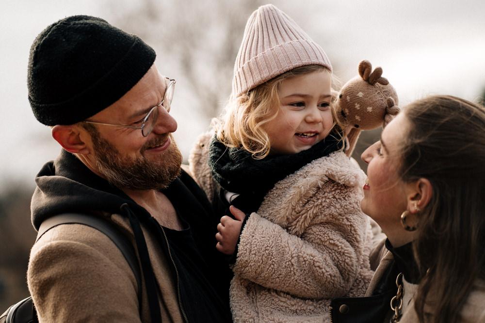 Tochter bei Mama und Papa auf dem Arm familienreportage